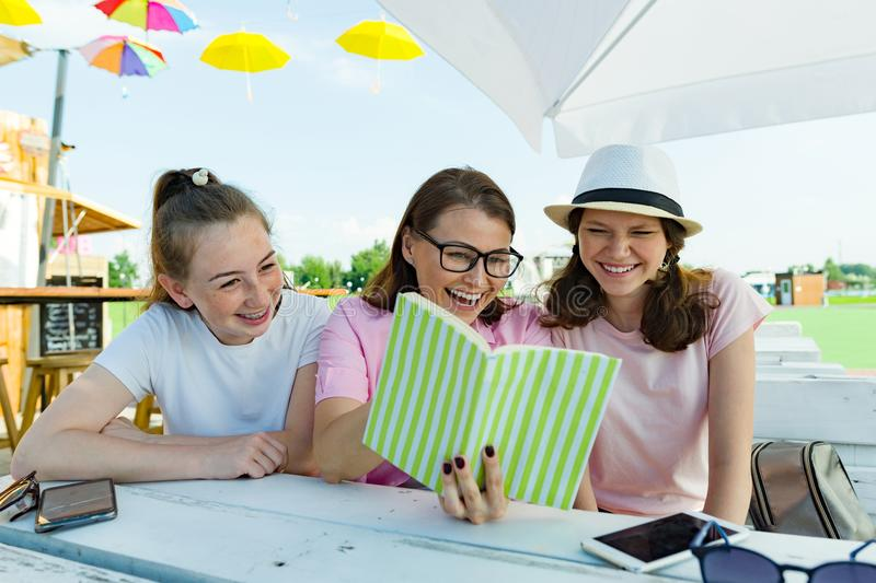 Mom and daughters teenagers have fun, look and read funny book. Communication of the parent and children of adolescents. royalty free stock image