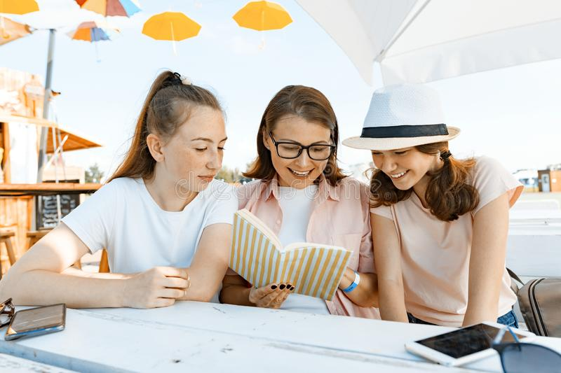 Mom and daughters teenagers have fun, talking, look and read funny book. Communication of the parent and children of adolescents. Sit in a street cafe, sunny royalty free stock photography