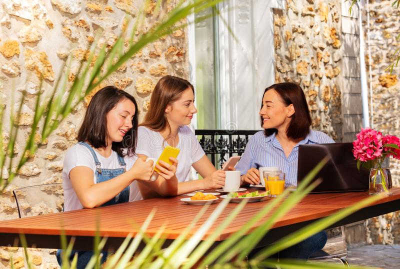 Mom and daughters using smartphone during lunch royalty free stock images