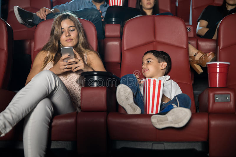 Mom distracted with phone at the movies. Portrait of a pretty young women using her smartphone and getting distracted while sitting in a movie theater with her stock photos