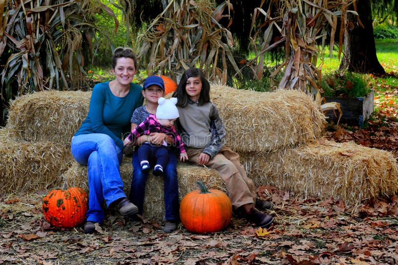 Mom and family in pumpkin patch. A sweet baby wearing a white sock hat and a mommie are in a pumpkin patch sitting on bales of hay. Shallow depth of field stock image