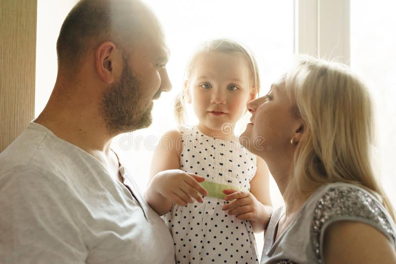 Mom, father and little daughter. Close-up portrait in backlight. stock photos