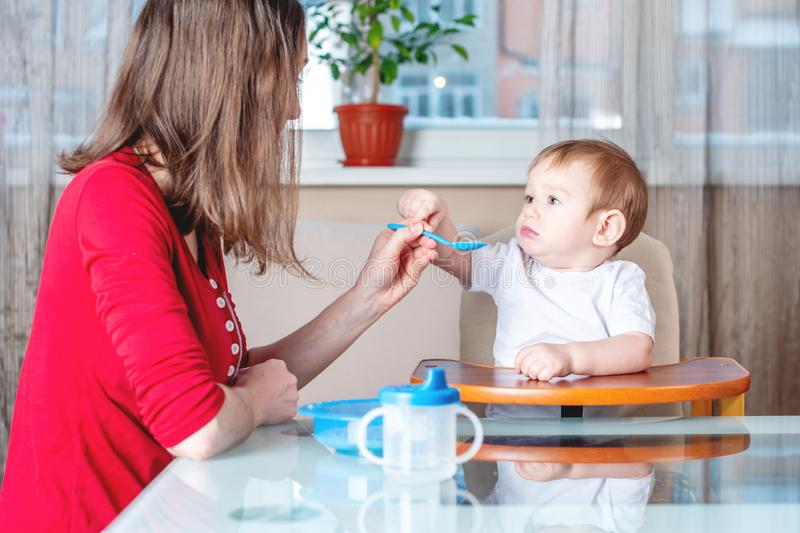 Mom feeding the baby holding hand with a spoon of food in the kitchen. Healthy baby nutrition. Emotions of a child. Mom feeding the baby holding out her hand stock images