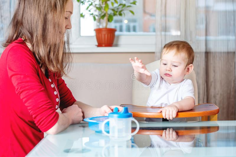 Mom feeding the baby holding hand with a spoon of food in the kitchen. Healthy baby nutrition. Emotions of a child. Mom feeding the baby holding out her hand royalty free stock photography