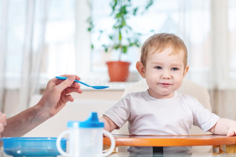 Mom feeding the baby holding hand with a spoon of porridge in the kitchen. Emotions of a child while eating healthy food stock photography