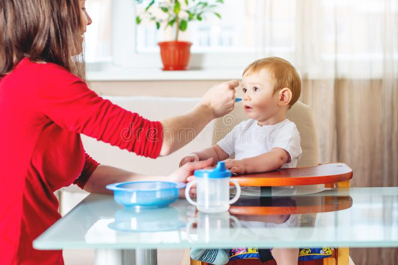 Mom feeding the baby holding out her hand with a spoon of food in the kitchen. Emotions of a child while eating stock photo
