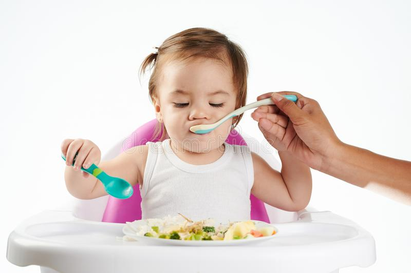 Mom feeding baby with spoon stock images