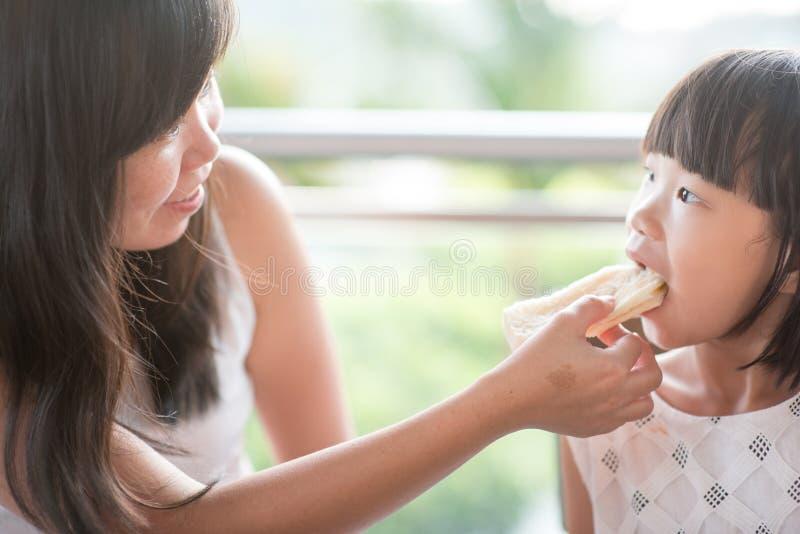 Mom feeding child bread royalty free stock photo