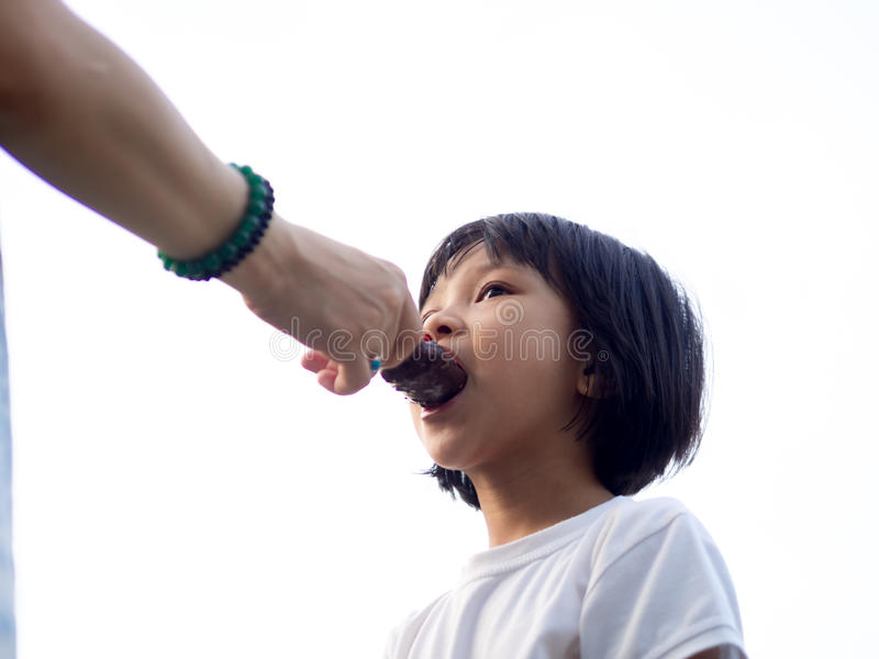 Mom Feeding Chinese Child an Ice Cream royalty free stock images