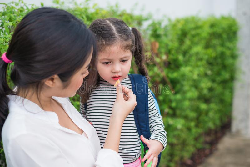 Mom feeding her daughter with snack before going to school. Back to school and Education concept. Home sweet home and happy family stock photo