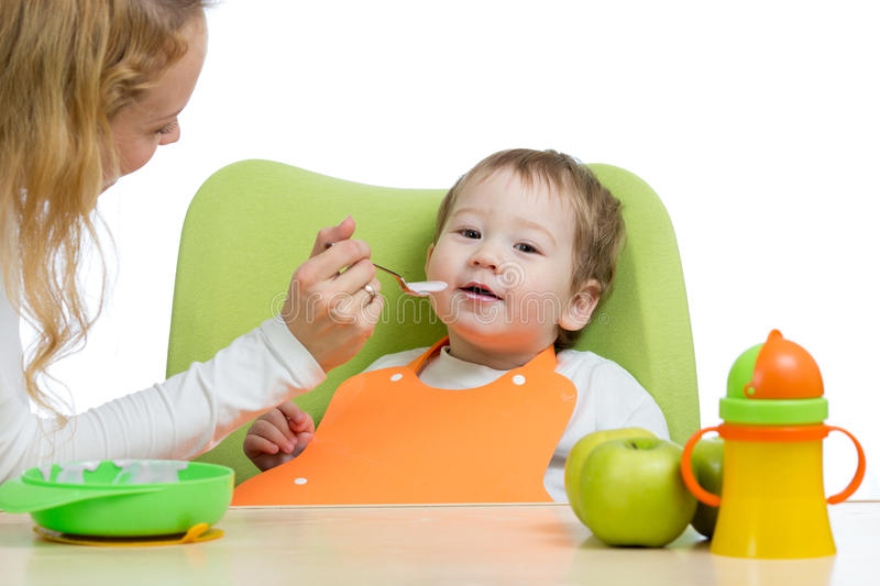 Mom feeding her kid with a spoon. Mother giving food to her little child. Baby food and nutrition. royalty free stock photo