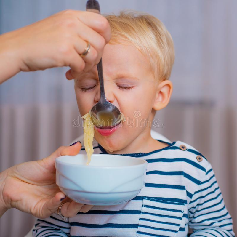 Mom feeding son. Boy cute baby eating breakfast. Child eat soup. Kid cute boy blue eyes sit at table with plate and food stock image