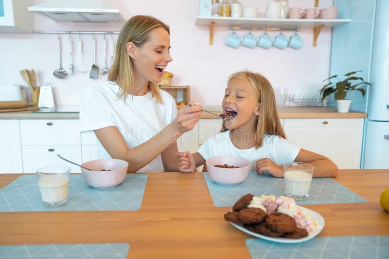 Mom feeds her beautiful daughter with chocolate flakes. have a good time together, dressed alike royalty free stock images