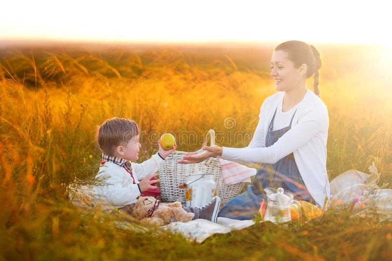 Mom feeds her son on a picnic. Mother and young son in sunny fall day. Happy family and healthy eating concept stock images