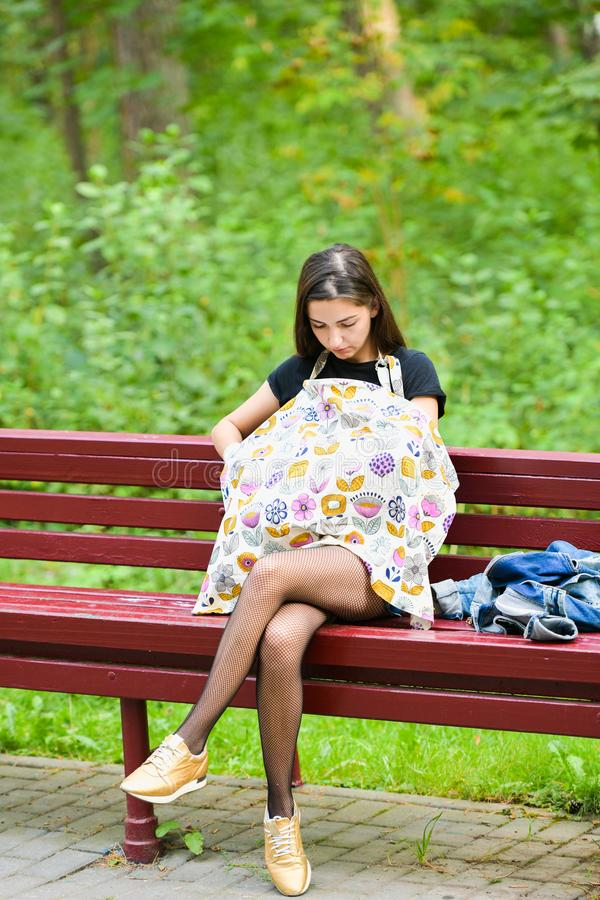 Mom feeds the newborn on the bench. covered with a diaper from prying eyes. Young woman, new mother breastfeeding and caring her stock photography