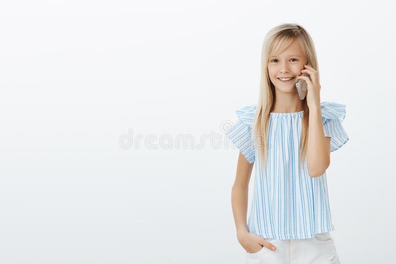 Mom gave daughter cellphone to talk with granny. Studio portrait of positive pleased european child with fair hair in stock photography