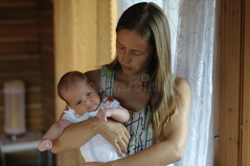Mom hugs her baby in her arms stock photos