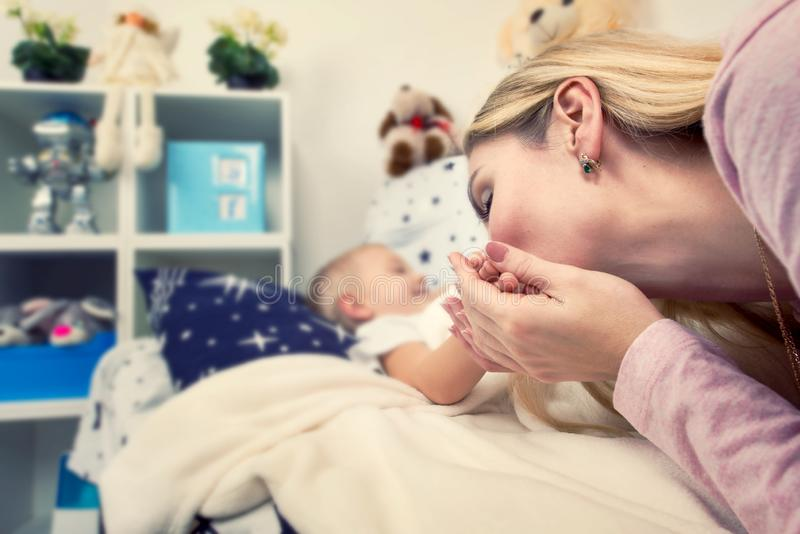 Mom gently kiss the hand of his little son before sleep.Happy childhood, love family. Happy childhood, love family.Mom gently kiss the hand of his little son royalty free stock photo