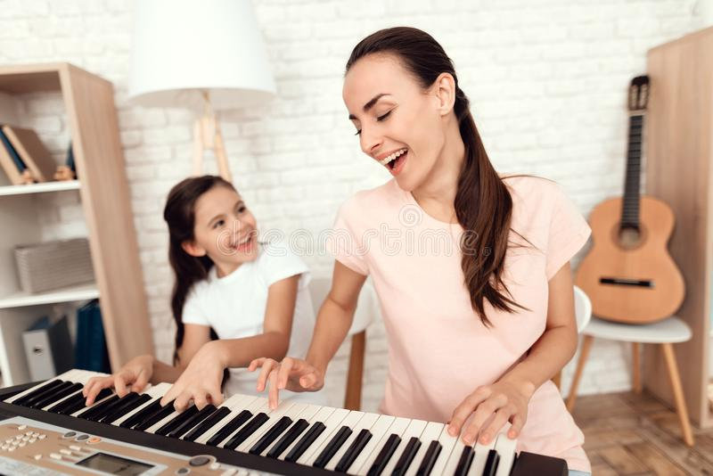 Mom and girl are playing the synthesizer at home. They rest and have fun. stock photos
