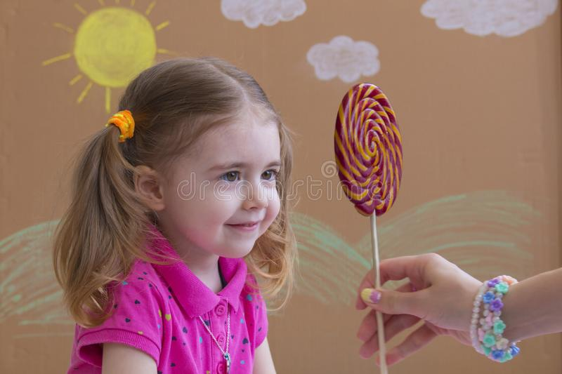 Mom gives the baby a lollipop, happy little girl eating big sugar lollipop, kid eat sweets. Beautiful little girl with stock photo