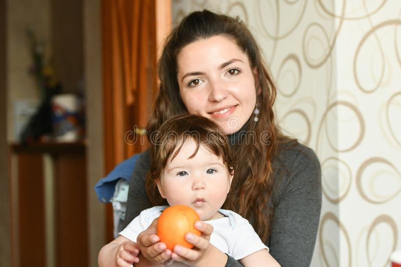 Mom gives the child an orange.Small child in an inflatable beach house near the river, takes an orange from the hands of mom stock photography