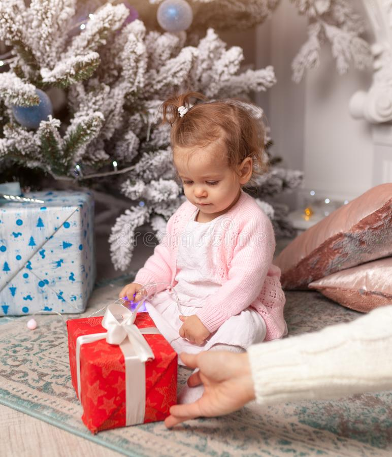 Mom gives a gift to her beloved little daughter for the new year. Christmas tree on the background stock photos