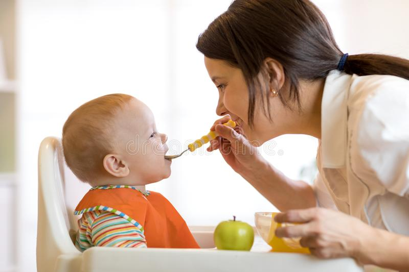 Mom giving fruit puree to her baby son on high chair. stock photos