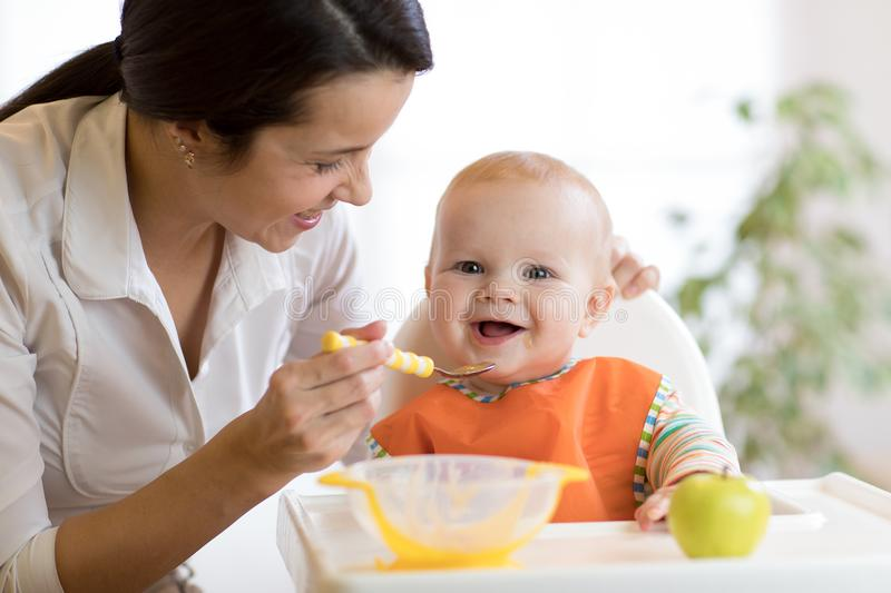 Mom giving homogenized food to her baby son on high chair. Mom giving homogenized food to her baby son on high chair in kitchen stock image
