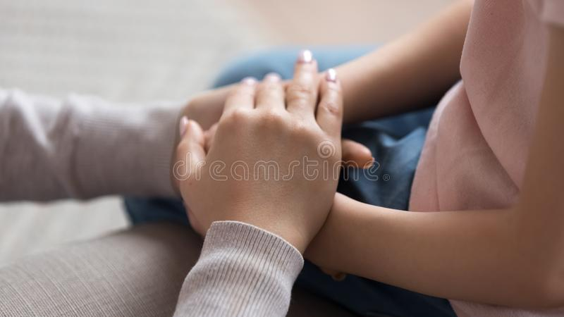 Mom giving support trust to little daughter holding hands, closeup royalty free stock photos