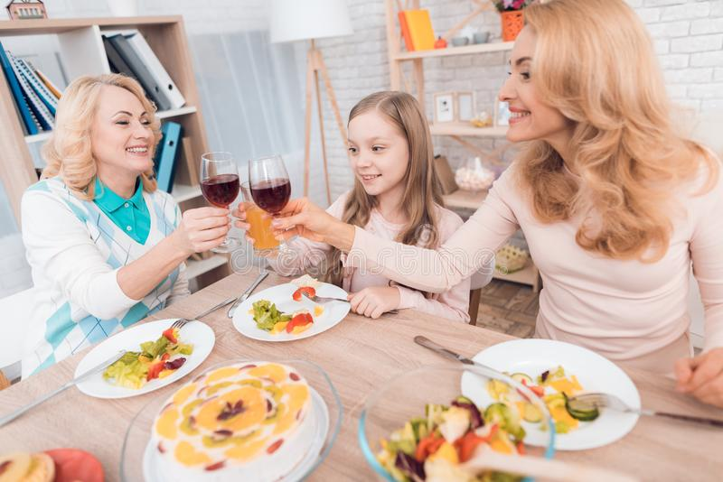 Mom and grandmother are drinking wine, a little girl is drinking juice. stock image