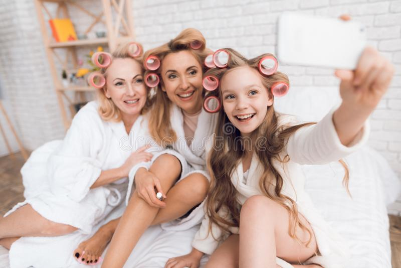 Mom, grandmother and girl in curlers do selfie on the phone. They are sitting on the bed in dressing gowns royalty free stock photos