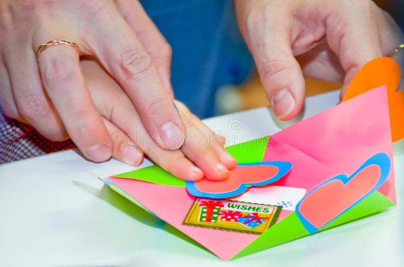 Mom hands guiding a child hands to help with making colorful cardboard crafts with hearts and word Wishes royalty free stock image
