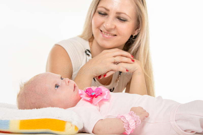 Mom with a happy smile looking at his baby daughter. A two-month baby lying on his back on the bed, sitting next to the child and mother looking at her royalty free stock photo