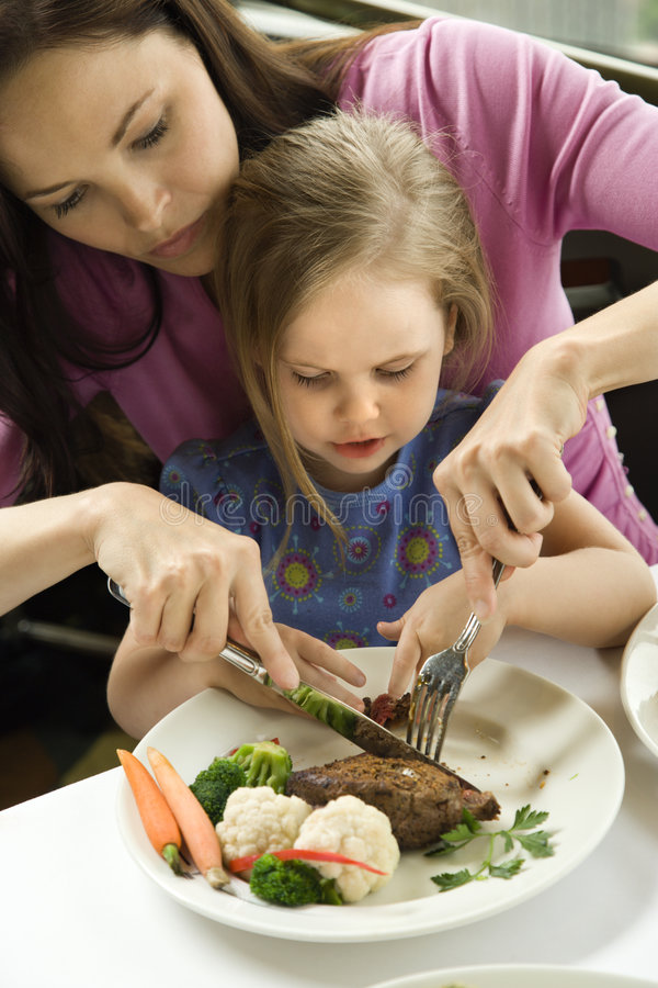 Mom helping daughter cut food. stock photos