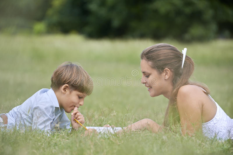 Mom helping son with homework, laying down on grass stock images
