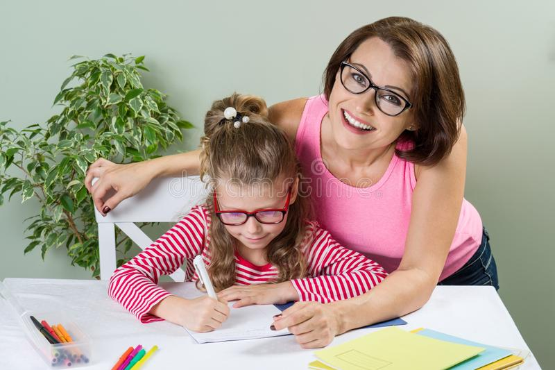 Mom helps the child write. Girl 6, 7 years old with glasses sitting at the table and writing in notebook stock photography