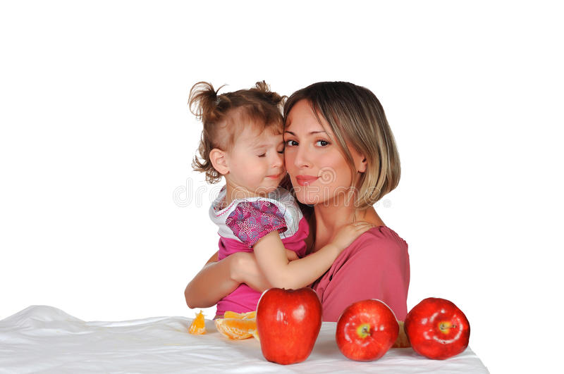 Mom and her daughter. Mom and her young daughter together eat fruits royalty free stock image