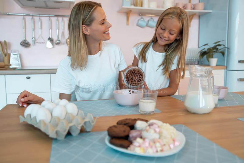 Mom with her daughter eating chocolate flakes. have a good time together, dressed alike.  stock image