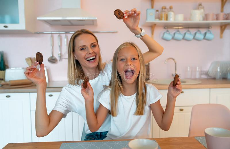 Mom with her daughter fooling around in the kitchen holding American chocolate chip cookies in her hands. dressed alike stock image