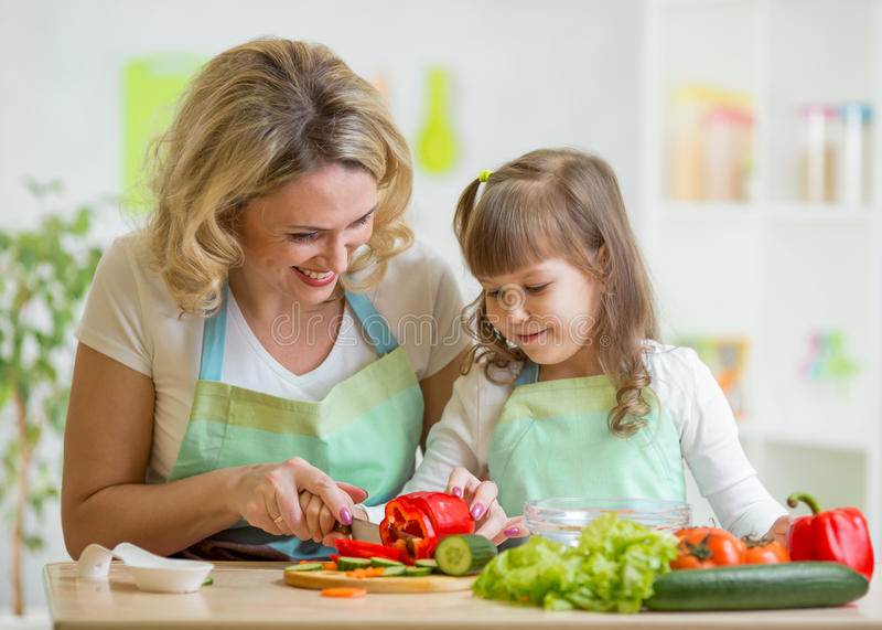 Mom and her daughter preparing vegetables at royalty free stock photos