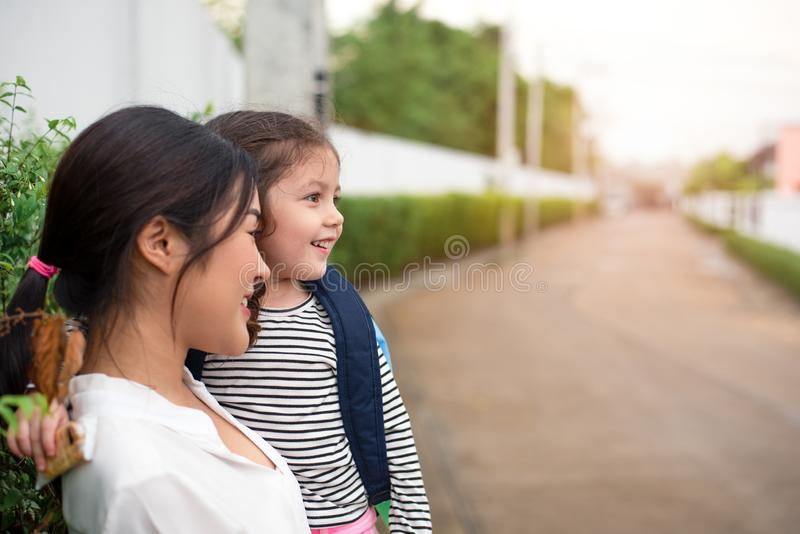 Mom and her daughter smiling together after going home from school. Love and daycare concept. Happy family and Home sweet home stock images