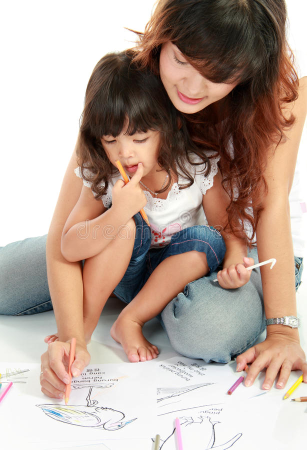 Mom and her little daughter drawing together stock images