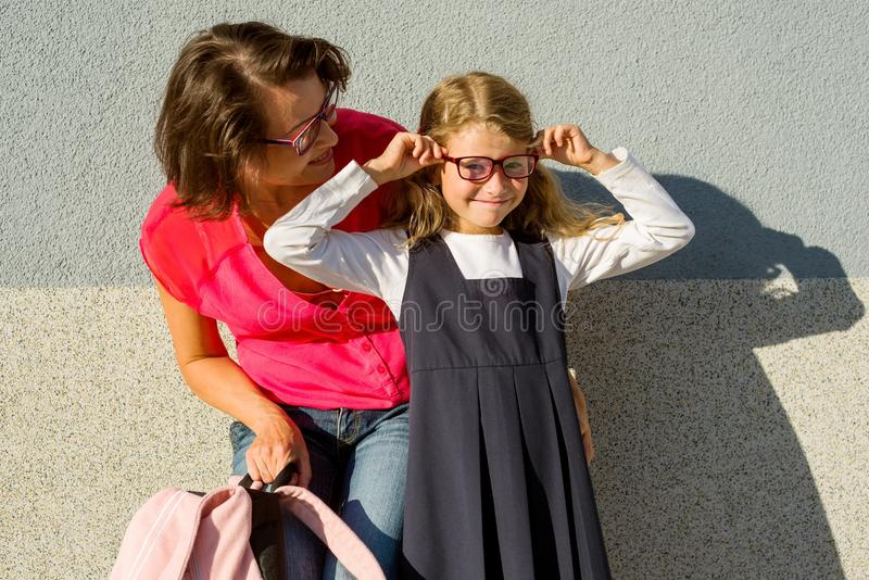 Mom and her little daughter, a student, enjoy socializing. royalty free stock images