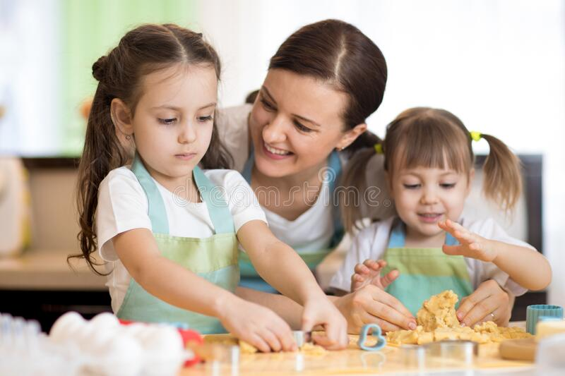 Mom with her little daughters are cooking holiday pie in the kitchen royalty free stock photography