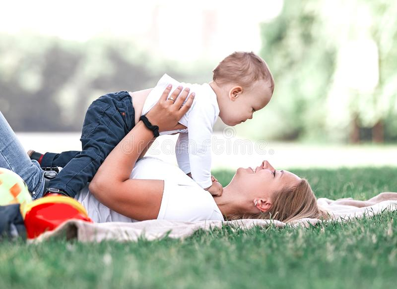 Mom and her little son play together, lying on the lawn . stock photos