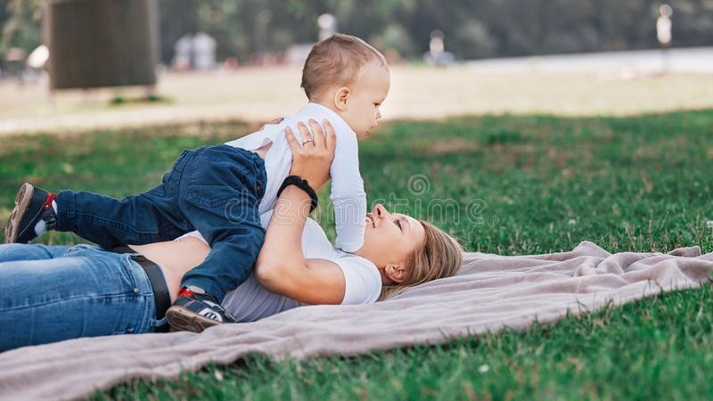 Mom with her little son playing on the lawn on a summer day. stock photo