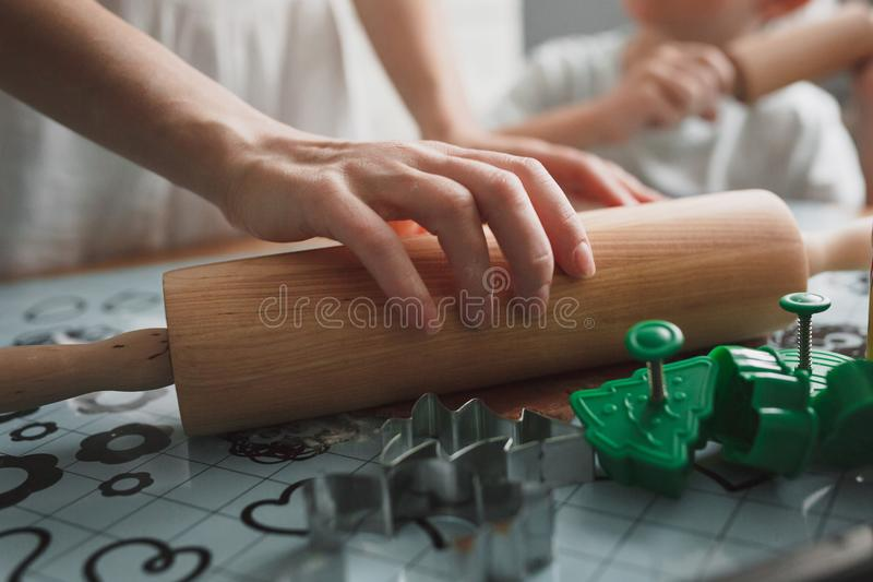Mom and her son cook cookies in the home kitchen. Close-up of female hands and kitchen appliances. stock photos