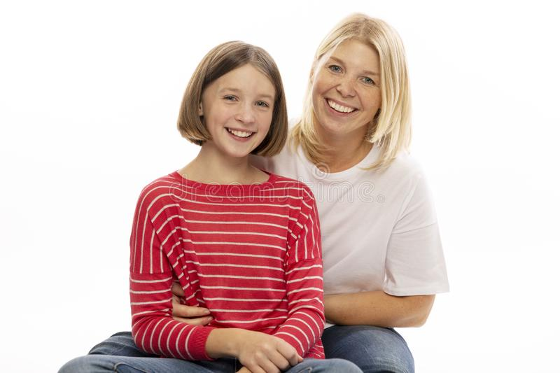 Mom with her teenage daughter hugging and laughing. White background royalty free stock photo