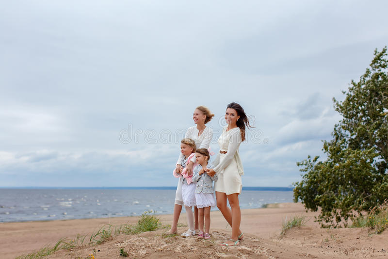 Mom and her three daughters hugging against the sea in windy weather, summer royalty free stock photography