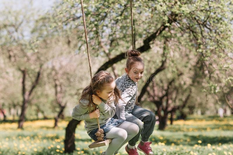 Mom and her two pretty daughters on a swing royalty free stock photography